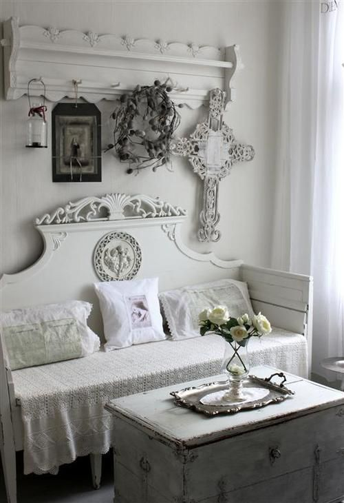 a white entryway, a carved clothes hanger, a carved bench, a chest for storage, signs and candle lanterns
