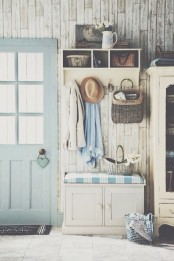 a beautiful shabby chic entryway with whitewashed wooden walls, a storage unit, a cabinet and a seat and a pastel door