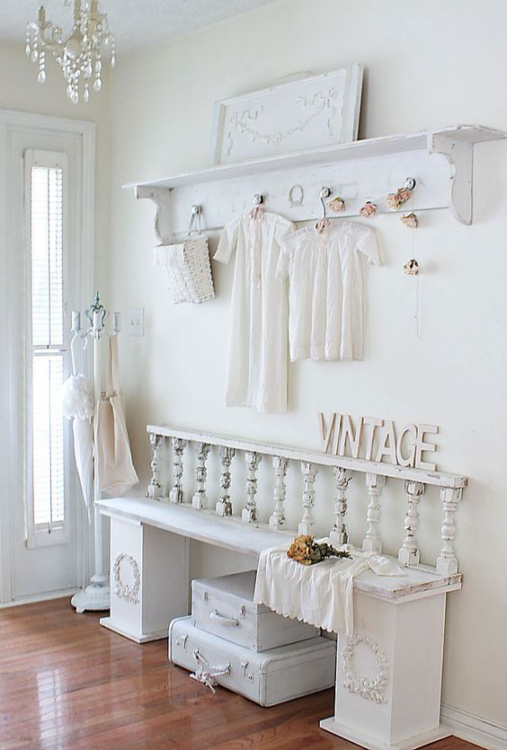 an all white shabby chic entryway with a clothes hanger, a bench, some suitcases under the bench and some cute clothes