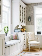 a neutral shabby chic entryway with a whole storage unit, a daybed, lamps, candle lanterns and a vintage chair
