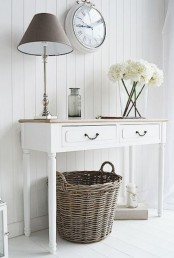 a neutral shabby chic entryway with a console, a table lamp, a clock and a basket for storage