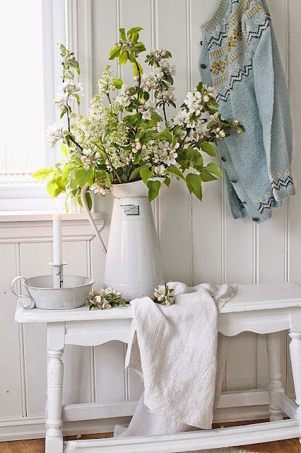 a white shabby chic entryway with a carved bench, a jug with green branches and some blankets