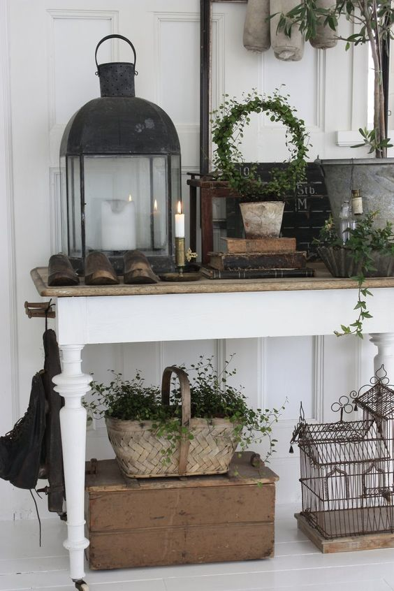 a shabby chic meets rustic entryway with a console table, boxes, candle lanterns, a basket and greenery all around
