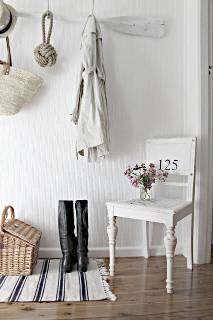 a beach meets shabby chic entryway with an oar as a clothes holder, a striped rug, a chair and a basket for storage