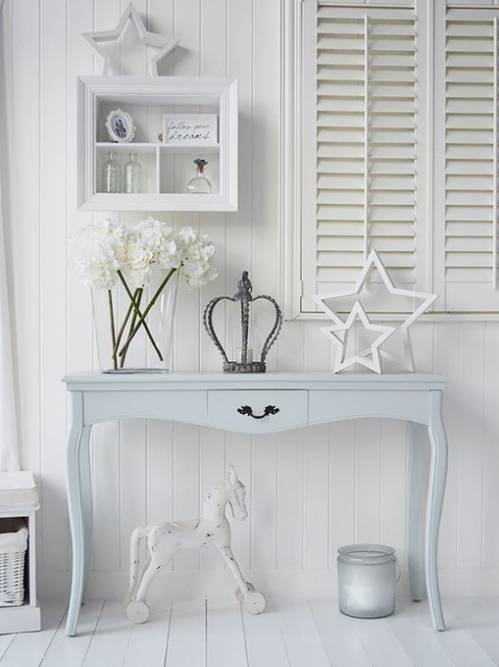 a cozy neutral shabby chic entryway with shutters, a pastel console table, a storage unit and a large candleholder