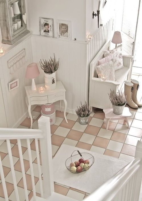a cozy neutral shabby chic entryway with a bench and a little console, potted blooms, a rough wood cabinet and photos