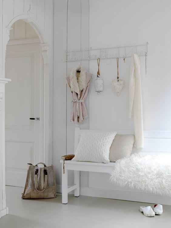a white shabby chic meets Nordic entryway with a holder on the wall and a bench with faux fur