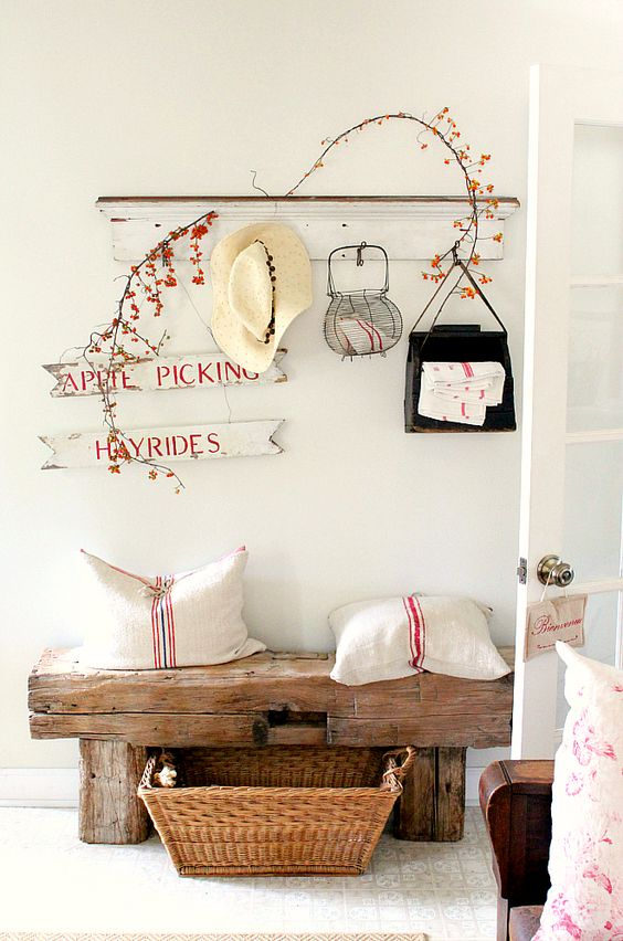 a rustic meets shabby chic entryway with a wooden bench, signs, a shelf, a basket for storage feels cozy