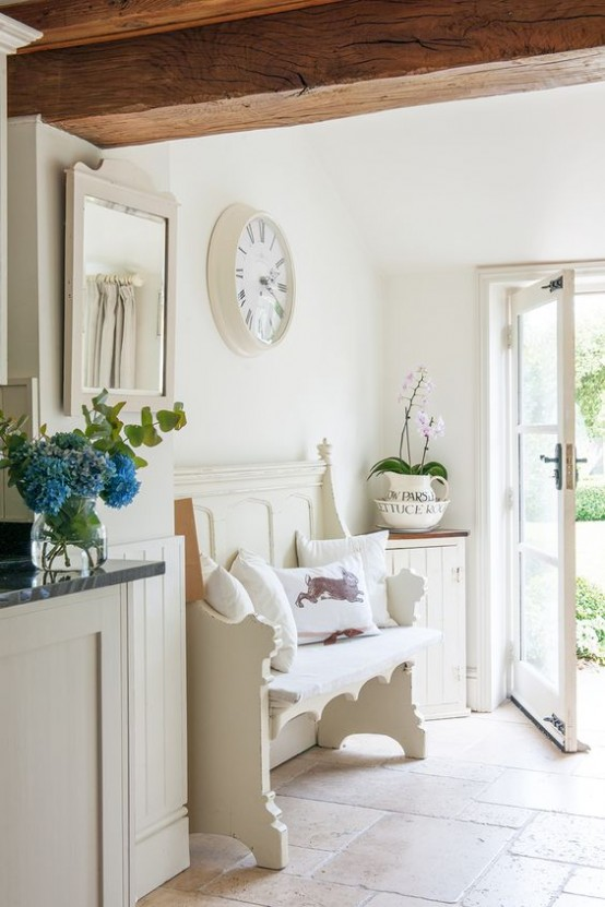 a neutral shabby chic entryway with a carved wooden bench, a vintage clock and a framed mirror