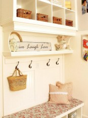 a neutral shabby chic meets farmhouse entryway with an open storage unit with a daybed, some signs and baskets for storage