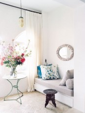 a neutral entryway with curtains, a pendant lamp, a cozy daybed, a mirror and a stool plus a stylish vintage coffee table