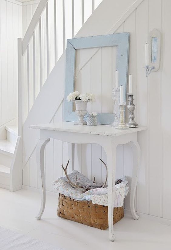 a white shabby chic entryway with an elegant console table, a blue frame, potted blooms and a basket for storage
