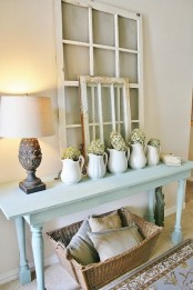 a shabby chic entryway with a powder blue console table, window frames, lamps and a basket under the table