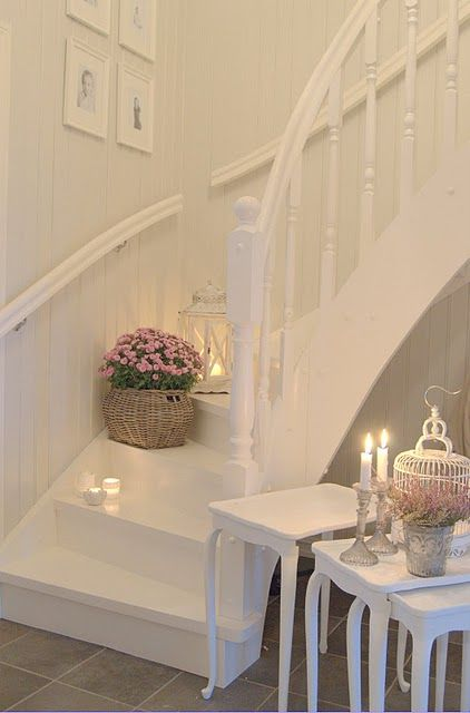 a white shabby chic entryway with side tables, candles, a cage and potted blooms