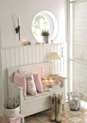 a neutral shabby chic entryway with shiplap on the wall, a porthole window, a wooden bench, potted greenery and a shutter door