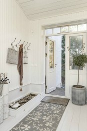 a neutral entryway with a pebble box for shoes, rugs, a potted tree and a clothes hanger