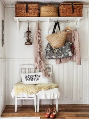 a shabby chic entryway with a shelf with baskets, chairs, woven bags anf cute clothes