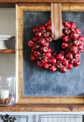 a cute and lush red apple and greenery fall wreath with a burlap ribbon is a cool rustic decor idea