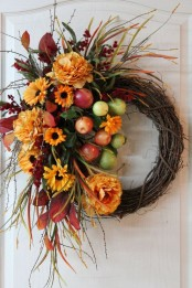 a bright and lush fall wreath of vine, faux blooms, leaves, twigs and apples looks bold and very cool