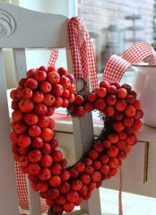 a red heart-shaped wreath of faux apples and with red plaid ribbons is a cool autumnal decoration for the fall