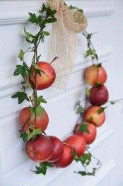 an all-natural mini wreath of natural apples and foliage plus a burlap bow is small, cute and very edible