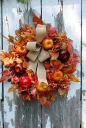 a bright fall wreath of faux foliage, bright apples and a burlap bow on top is a cool idea that will last long