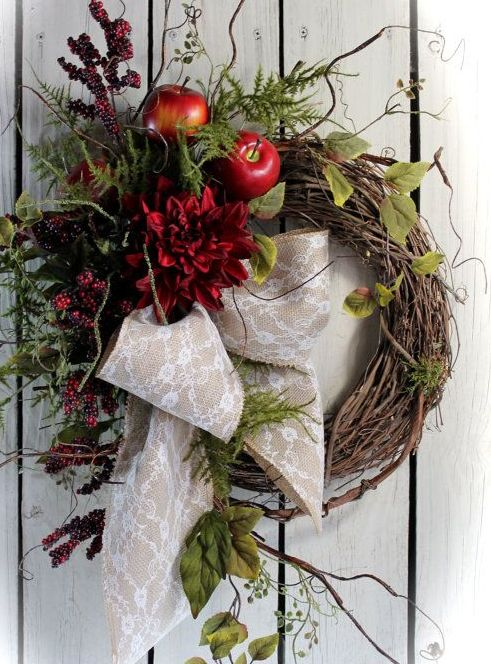 a wild fall wreath of vine with faux greenery, leaves, twigs, berries, apples and burgundy blooms plus a burlap and lace bow