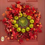 a super bold fall wreath of bright red leaves, dried blooms, cabbage and green apples is very farm-like