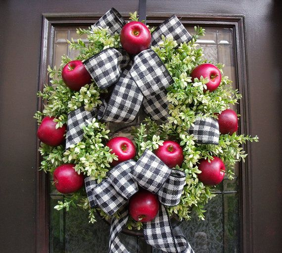 a bright and chic fall wreath of faux greenery, red apples and plaid irbbons and bows for cozy fall decor
