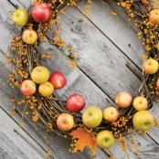 a natural fall wreath of vine, with mini apples and branches with berries is bright and fun and can be easily assembled
