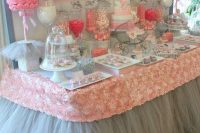 a grey and pink dessert table with tulle, fabric roses, fake floral arrangements and a polka dot backdrop