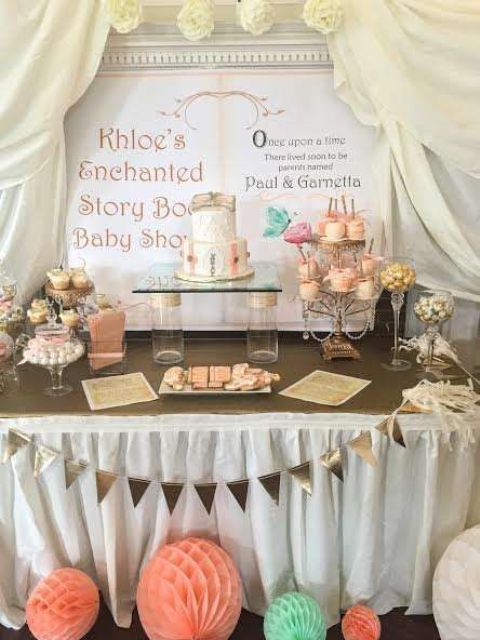 a gender neutral dessert table done in mint and coral, with a framed sign showing a story book and curtains