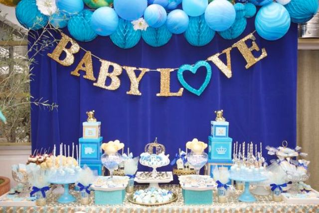a bold blue and gold dessert table with blue balloons and pompoms, a letter banner and bright blue and gold stands