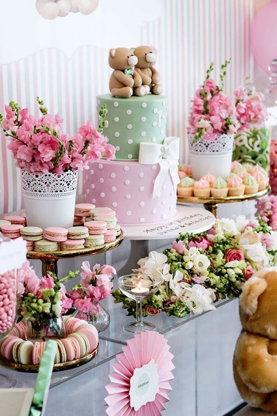 a bright pink and green baby shower with bright florla arrangements, colorful macarons and a cute two color cake with teddy bears