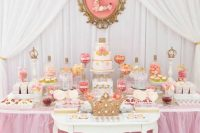 a bright pink and peachy pink dessert table with fake florals, bright candies and sweets and a royal feel in decor