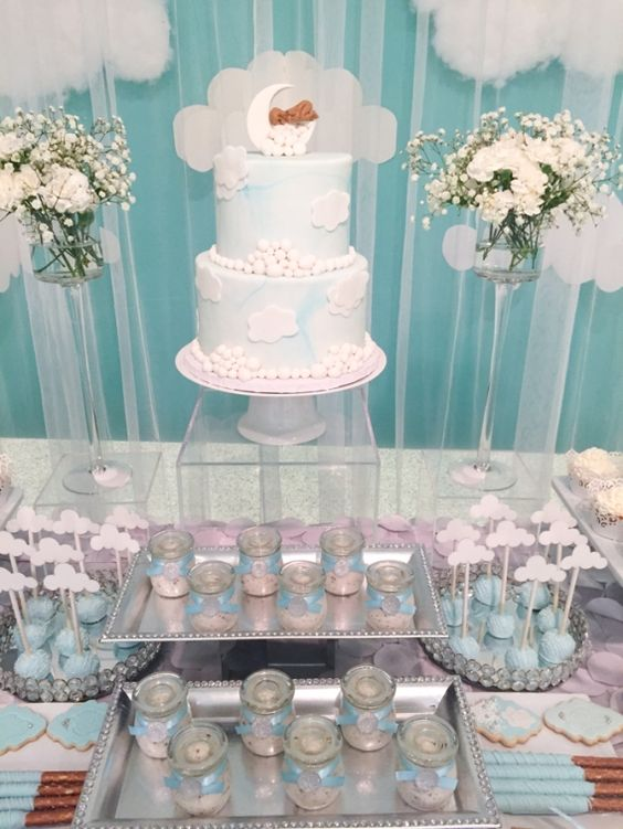 a blue and white dessert table with white floral arrangements, fake clouds, blue and white desserts and a cake