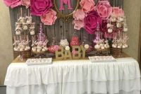 a rustic vintage dessert table with a reclaimed wood wall backdrop, large pink paper blooms, a ruffled tablecloth and lots of pink desserts