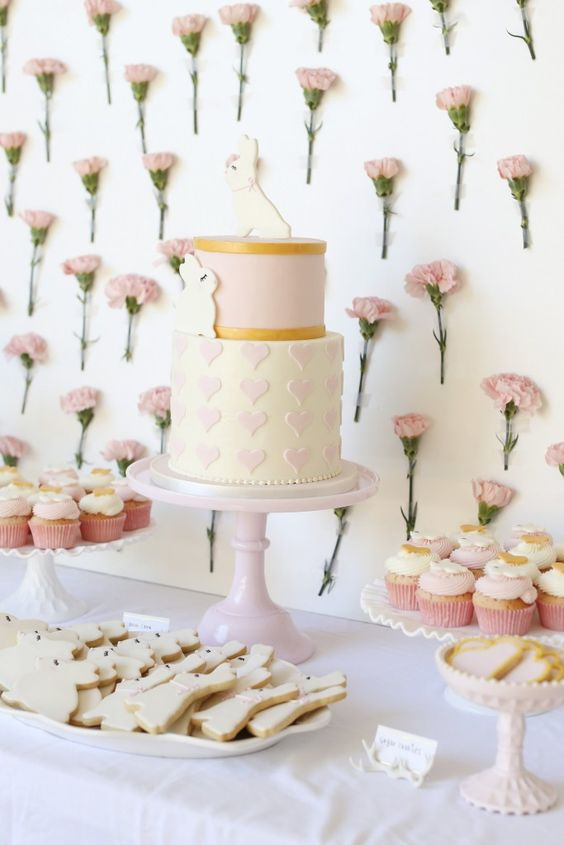 a girlish dessert table with a fresh flower wall and delicious sweets on stands and plates