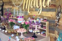 a super colorful dessert table done with purple, pink and turquoise touches, feathers, garlands and a dream catcher for a boho feel
