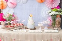 a colorful pink and fuchsia dessert table with paper pompoms and fans, colorful floral arrangements and a bright tassel garland