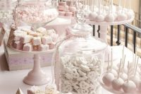 a light pink and white dessert table styled with lots of stands, jars and some signs to mark the sweets