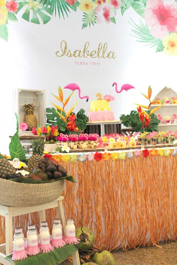 a tropical dessert table with touches of yellow, pink, green, orange, flamingos and fruits in a basket