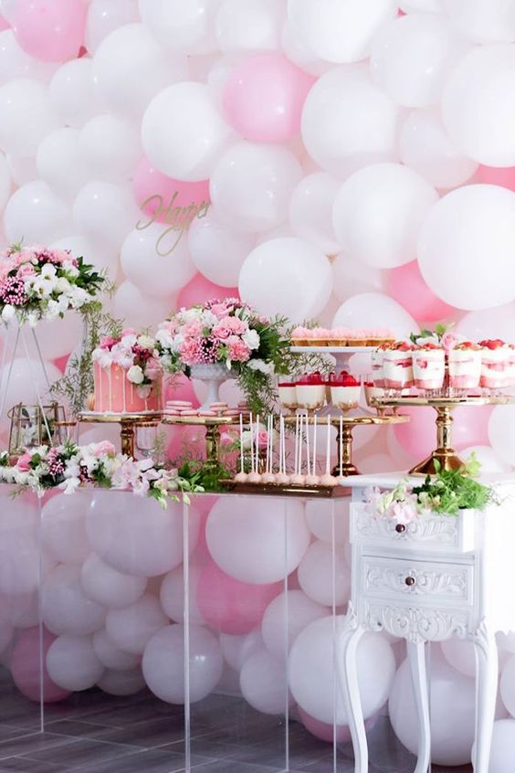 a girlish dessert table with a pink and white balloon wall, bright pink and white floral arrangements, pink desserts and a drip cake