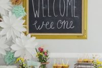 a bright dessert table styled with a framed chalkboard sign, paper flowers and pompoms and simple wildflower centerpieces