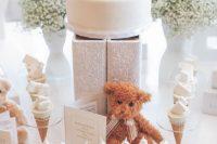 a neutral dessert table with baby's breath, a teddy bear, a teddy bear cake looks totally gender neutral