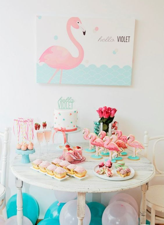 a colorful aqua and pink dessert table with flamingos, pink roses, a polka dot cake and a flamingo art piece
