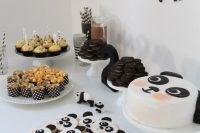 a fun panda-inspired dessert table with a panda banner, panda cookies and a cake plus some black and white sweets