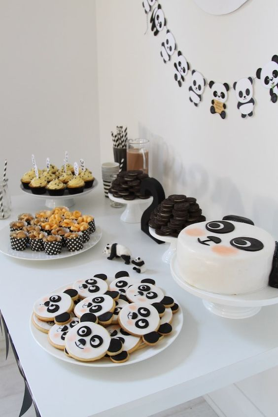 a fun panda inspired dessert table with a panda banner, panda cookies and a cake plus some black and white sweets