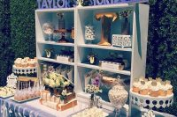 an off-white and grey dessert table with a box-shaped shelf and lots of sweets on stands and even on books