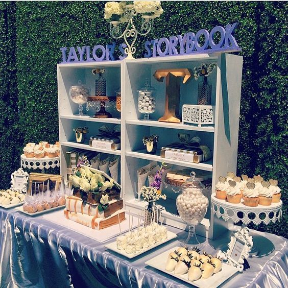 an off white and grey dessert table with a box shaped shelf and lots of sweets on stands and even on books